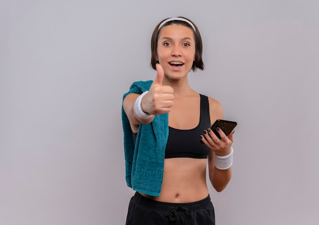 Giovane donna fitness in abiti sportivi con il tovagliolo sulla spalla che tiene smartphone sorridente che mostra i pollici in su in piedi sopra il muro bianco