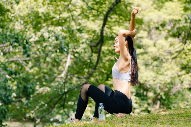 ツリーの下で体を伸ばして若いフィットネス女性。