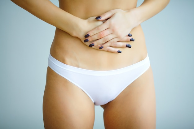 Young fitness woman suffering from a stomach pain