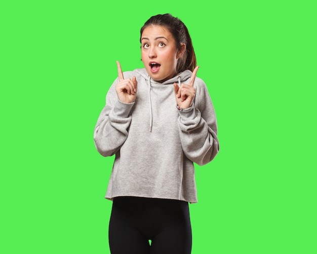 Young fitness woman surprised pointing up to show something