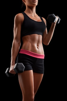 Young fitness woman in training pumping up muscles with dumbbell