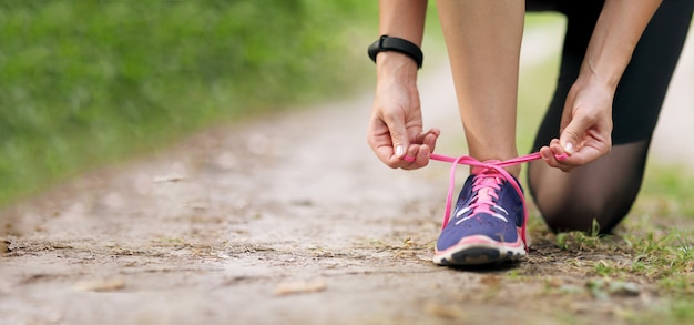 Young fitness woman tying shoelace running sneakers. healthy fit living.