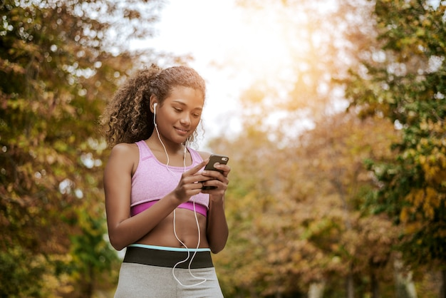 Young fitness woman using phone after running outdoors in park.
