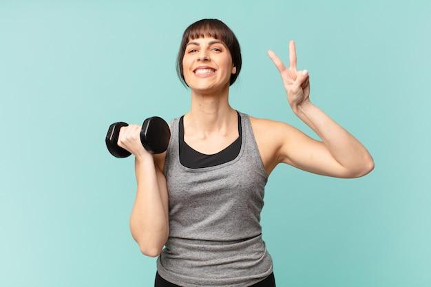Молодая женщина фитнеса с гантелями