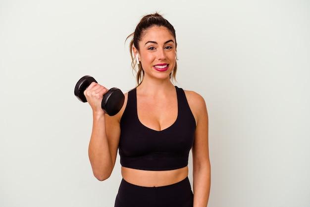 Молодая женщина фитнеса с гантелями изолирована на белой стене