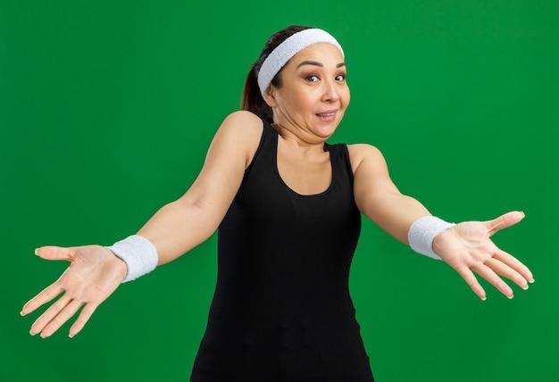 머리띠와 완장을 가진 젊은 피트 니스 여자는 녹색 벽 위에 서서 불만과 분노에 팔을 밖으로 혼동