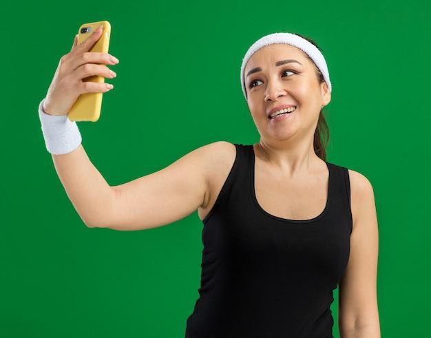 머리띠와 완장 행복하고 긍정적 인 젊은 피트 니스 여자 녹색 벽 위에 서있는 스마트 폰을 사용하여 셀카를하고 웃고