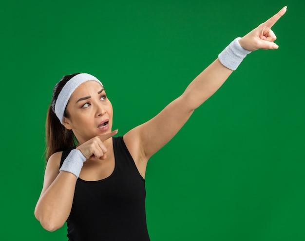 緑の壁の上に立って人差し指で指している深刻な顔でよそ見ヘッドバンドと腕章を持つ若いフィットネス女性