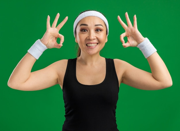 머리띠와 완장이 녹색 벽 위에 서있는 확인 표시를 유쾌하게 보여주는 젊은 피트 니스 여자