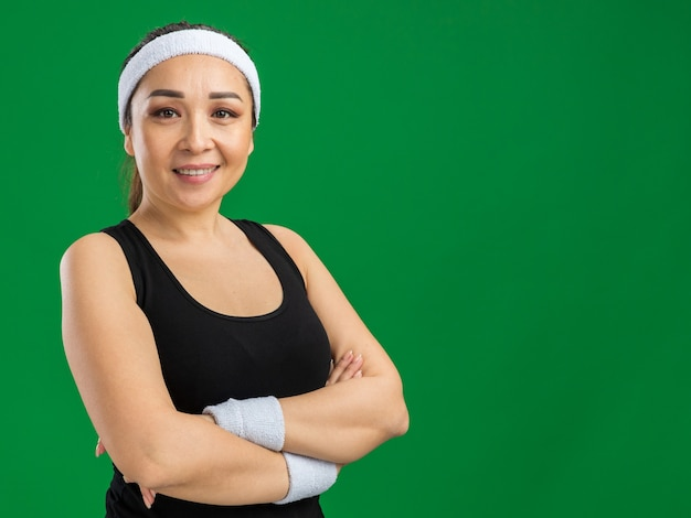 머리띠와 팔에 자신감 미소 완장 젊은 피트 니스 여자는 녹색 벽 위에 서 넘어