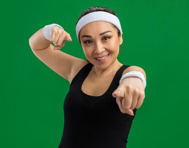 緑の壁の上に人差し指を立てて幸せそうな顔をして微笑むヘッドバンドと腕章を持つ若いフィットネス女性