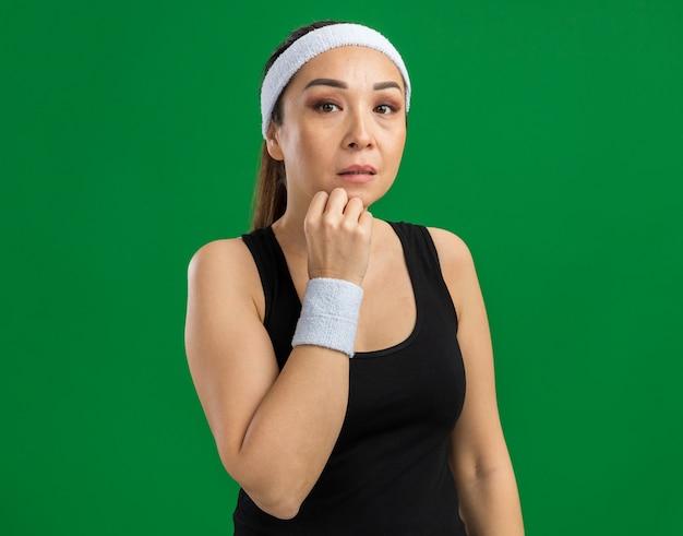 녹색 벽 위에 서있는 턱에 손으로 생각에 잠겨있는 표정으로 머리띠와 완장 젊은 피트 니스 여자