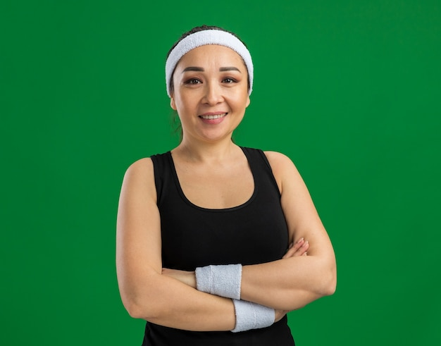 緑の壁の上に立って腕を組んで顔に笑顔でカチューシャと腕章を持つ若いフィットネス女性