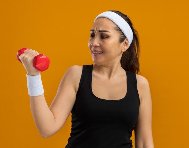 Giovane donna fitness con fascia e bracciali che tengono il manubrio guardandolo confuso e dispiaciuto in piedi sul muro arancione orange