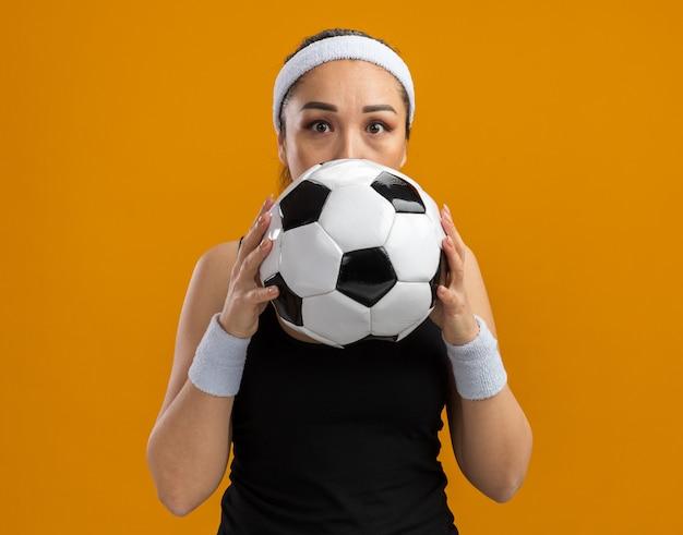 Giovane donna fitness con fascia e bracciali che tengono il pallone da calcio davanti al viso preoccupata in piedi sul muro arancione