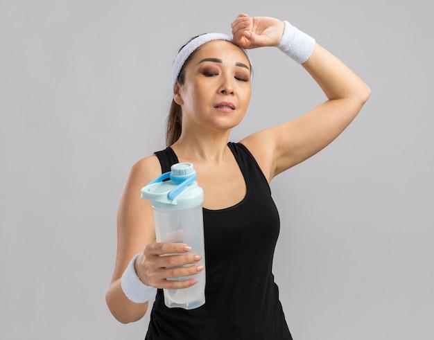 Giovane donna fitness con fascia e bracciali che tengono una bottiglia d'acqua che sembra stanca in piedi su un muro bianco
