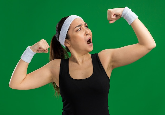Giovane donna fitness con fascia e bracciali che sembrano tesi alzando i pugni che mostrano i bicipiti in piedi sul muro verde green