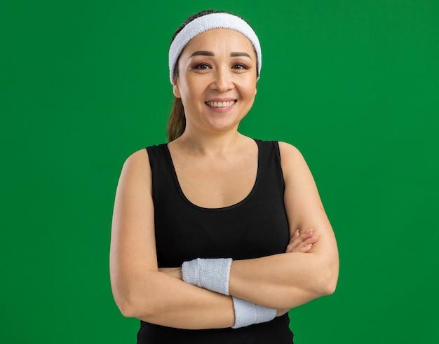 Giovane donna fitness con fascia e bracciali sorridente sicura di sé con le braccia incrociate in piedi sul muro verde green