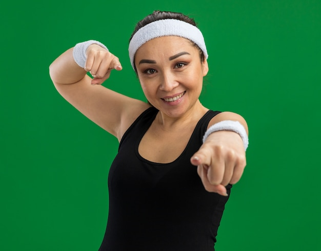 Giovane donna fitness con fascia e bracciali che sorride con la faccia felice che punta con l'indice in piedi sul muro verde green