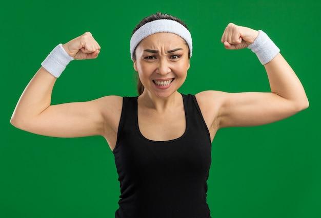 Giovane donna fitness con fascia e bracciali tesi e fiduciosi che alzano i pugni che mostrano forza e potenza in piedi sul muro verde