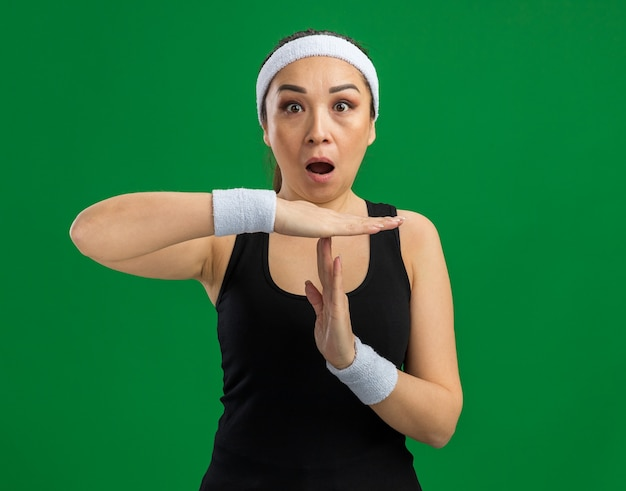 Giovane donna fitness con fascia e bracciali sorpresa a fare un gesto di pausa con le mani in piedi sul muro verde green