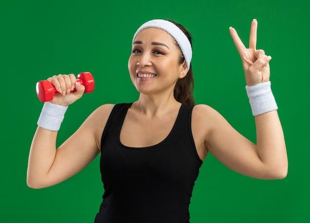 Giovane donna fitness con fascia con manubri che fa esercizi sorridendo mostrando il segno v in piedi sul muro verde green