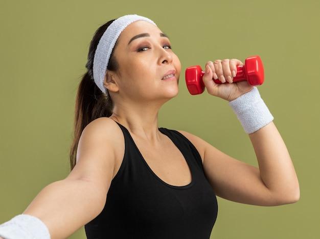 Giovane donna fitness con fascia con manubri che fa esercizi con espressione sicura in piedi sul muro verde