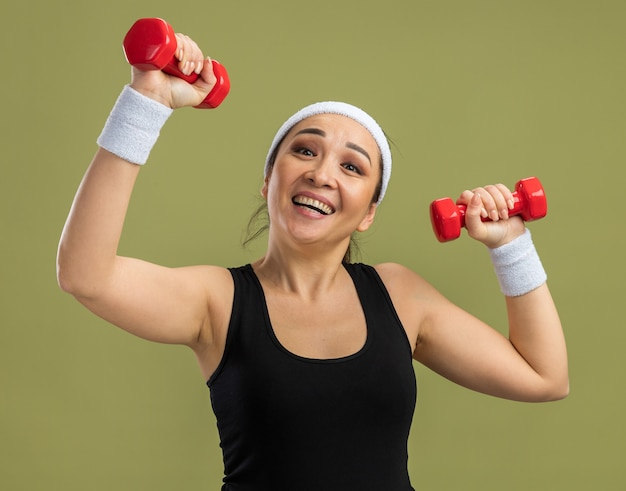 Young fitness woman with headband with dumbbells doing exercises happy and excited standing over green wall