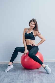 Young fitness woman with red fitball