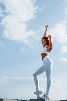 Молодая женщина фитнеса с стройным типом телосложения на открытом воздухе