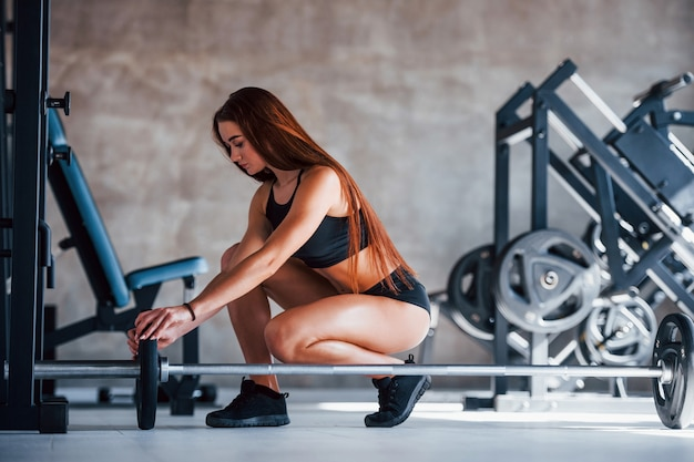 Young fitness woman with slim type of body and in black sportive clothes is in the gym with barbell.