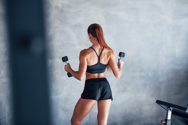 Young fitness woman with slim type of body and in black sportive clothes is in the gym.