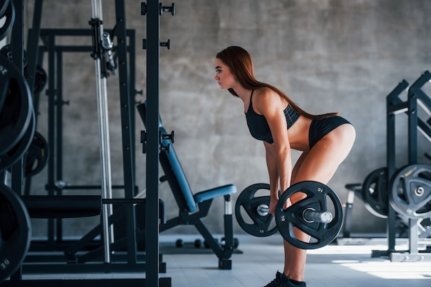 Young fitness woman with slim type of body doing exercises by using barbell.