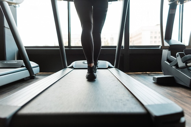スポーツウェアとスニーカーを持った若いフィットネス女性がジムのトレッドミルで実行されます