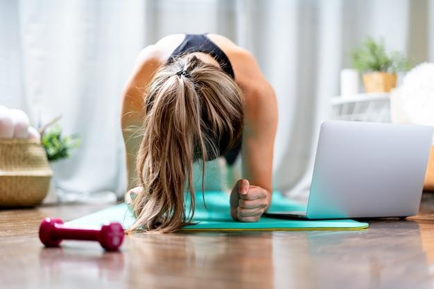 Молодая женщина фитнеса, работающая и использующая ноутбук и гантели дома в гостиной, занимаясь йогой или
