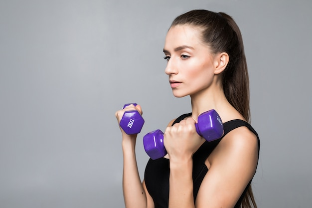Young fitness woman working out with dumbbell isolated on white wall