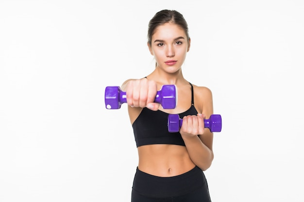 Young fitness woman working out with dumbbell isolated white wall
