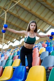 도시 경기장에서 아령으로 운동하는 젊은 피트 니스 여자. 스포츠 컨셉