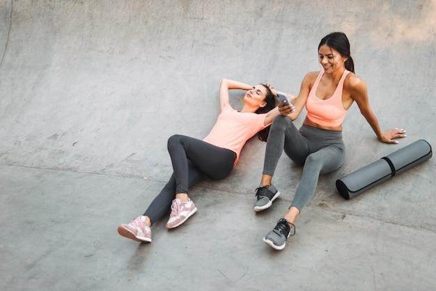 콘크리트 운동장에 앉아있는 동안 운동복 휴식과 핸드폰을 들고있는 젊은 피트니스 여성