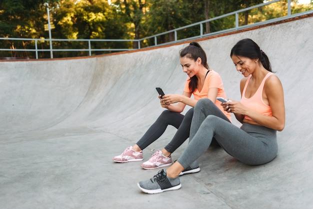 콘크리트 운동장에 앉아있는 동안 미소하고 핸드폰을 함께 들고 운동복에 젊은 피트 니스 여성