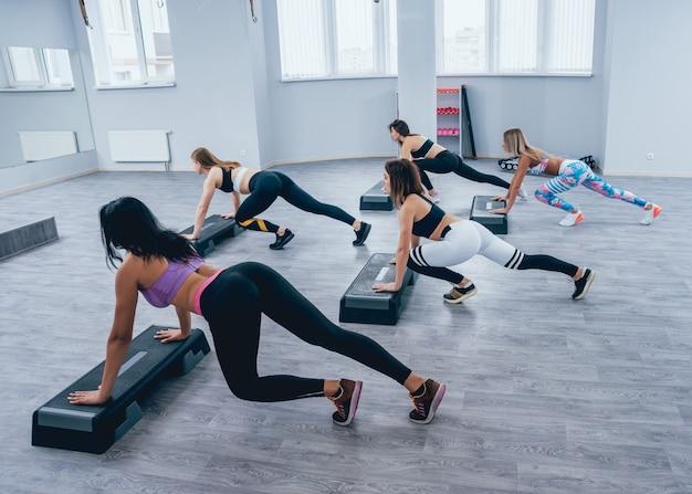 Молодые женщины фитнеса используя платформу шага на спортзале.