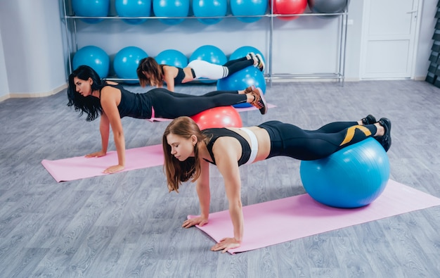 Young fitness women with blue fitballs.