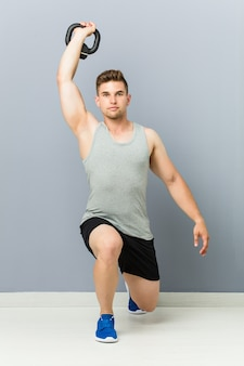Young fitnesss caucasian man holding dumbbell.