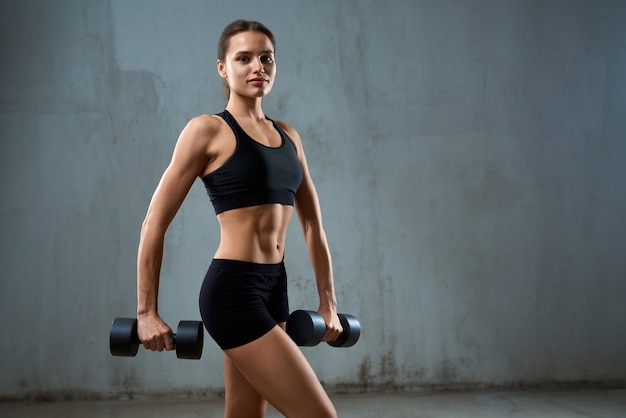 Молодая фитнес-женщина позирует с гантелями