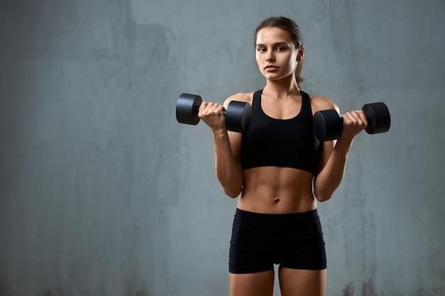 Молодая фитнес-женщина тренирует руки с гантелями