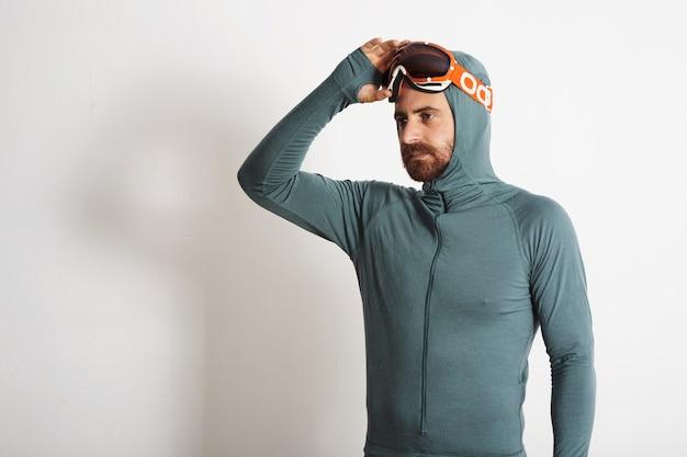 Giovane atleta maschio barbuto montato nella suite termica dello strato base rimuove i suoi occhiali da snowboard con una mano, isolata su bianco