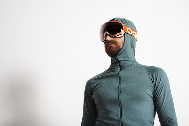 Young fitted bearded male athlete in baselayer thermal suite wears snowboarding googles, poses isolated on white