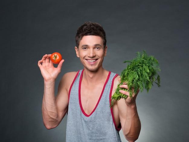 Молодой фитнес-тренер и диетолог, держащий миску с овощами на черном фоне