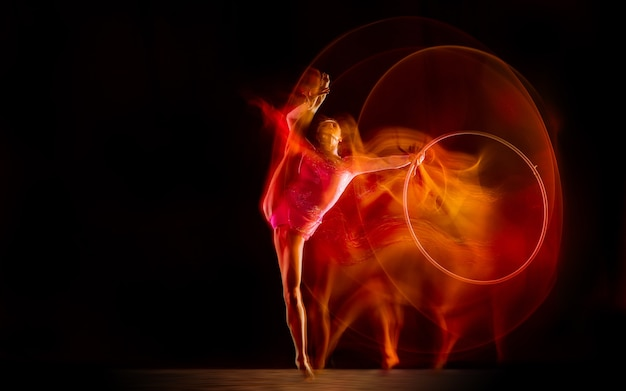 混合光の中で黒いスタジオの背景に分離された若い柔軟な女性体操選手