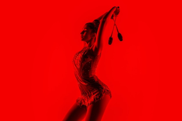 Giovane ginnasta femminile flessibile isolata sul rosso